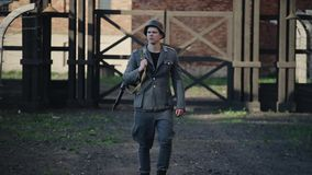 Ένας νέος όμορφος αρσενικός δράστης έντυσε καθώς ένας γερμανικός στρατιώτης περπατά προς τη κάμερα Η αναδημιουργία ενός στρατοπέδ απόθεμα βίντεο