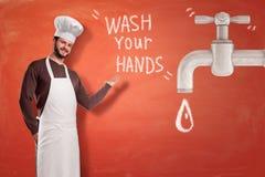 """Ένας νέος όμορφος αρχιμάγειρας στο αριστερό που δείχνει στο """"πλύσιμο τον τίτλο των χεριών σας στο κέντρο, με μια μεγάλη γκρίζα βρ στοκ φωτογραφία με δικαίωμα ελεύθερης χρήσης"""