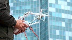 Ένας νεαρός άνδρας ένα άτομο ελέγχει ένα quadrocopter με έναν σύγχρονο πίνακα ελέγχου και μια συσκευή αποστολής σημάτων RC Πέταγμ φιλμ μικρού μήκους