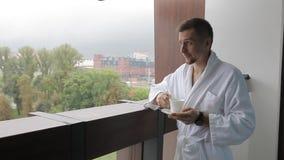 Ένας νεαρός άνδρας, ένα άτομο σε ένα άσπρο παλτό, πίνει τον καφέ στο μπαλκόνι απόθεμα βίντεο