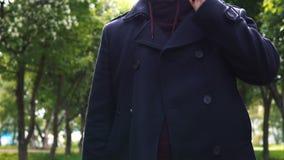 Ένας νεαρός άνδρας έντυσε σε ένα μαύρο παλτό που μιλά σε ένα κινητό τηλέφωνο στο πάρκο φιλμ μικρού μήκους