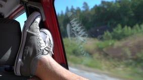 Ένας νεαρός άνδρας απολαμβάνει με το αυτοκίνητο ρίχνει τα πόδια της στο παράθυρο απόθεμα βίντεο