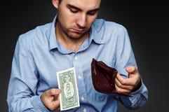 Ένας νεαρός άνδρας δείχνει ότι έχει στο πορτοφόλι ένα ένα δολάριο Στοκ Φωτογραφίες