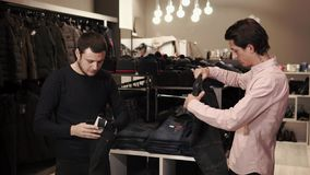 Ένας νεαρός άνδρας εξετάζει τα τζιν για την αγορά, ο πωλητής τον βοηθά απόθεμα βίντεο