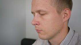 Ένας νεαρός άνδρας εργάζεται σε μια συνεδρίαση lap-top σε έναν μαύρο καναπέ απόθεμα βίντεο
