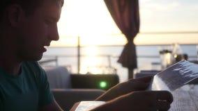 Ένας νεαρός άνδρας κάθεται σε έναν καφέ στην ακτή με Zakia, φυλλομετρεί τις επιλογές, θέλει να κάνει μια επιλογή HD, 1920x1080 αρ απόθεμα βίντεο