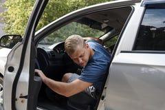 Ένας νεαρός άνδρας κάθεται σε ένα αυτοκίνητο στοκ εικόνα με δικαίωμα ελεύθερης χρήσης