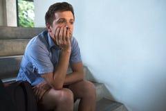 Ένας νεαρός άνδρας κάθεται στα σκαλοπάτια και λυπημένος Έχασε τα κλειδιά στο διαμέρισμα, στοκ εικόνες