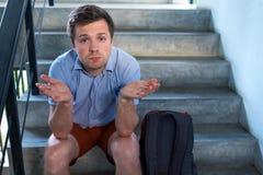 Ένας νεαρός άνδρας κάθεται στα σκαλοπάτια και λυπημένος Έχασε τα κλειδιά στο διαμέρισμα, στοκ εικόνα με δικαίωμα ελεύθερης χρήσης