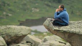 Ένας νεαρός άνδρας κάθεται στην άκρη ενός απότομου βράχου και παίζει τη φυσαρμόνικα απόθεμα βίντεο