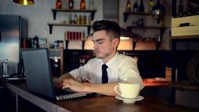 Ένας νεαρός άνδρας κάθεται στην κουζίνα στο μετρητή φραγμών και εργάζεται σε ένα lap-top απόθεμα βίντεο
