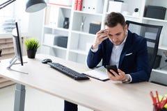 Ένας νεαρός άνδρας κάθεται στο γραφείο στον πίνακα, εξετάζει το τηλέφωνο και κρατά ένα μολύβι στο χέρι του Ο νεαρός άνδρας έχει Στοκ Εικόνες