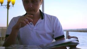 Ένας νεαρός άνδρας κάθεται το βράδυ σε έναν καφέ, φυλλομετρεί μέσω των επιλογών, χτυπήματα ενός ελαφριά αέρα HD, 1920x1080 κίνηση φιλμ μικρού μήκους