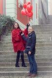 Ένας νεαρός άνδρας και μια νέα γυναίκα με τα κόκκινα εξαρτήματα α Στοκ Φωτογραφίες