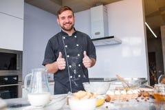 Ένας νεαρός άνδρας, ένας μάγειρας σε μια ποδιά, μαγειρεύει στην κουζίνα, όλες στο αλεύρι στοκ εικόνες