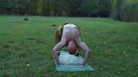 Ένας νεαρός άνδρας με έναν γυμνό κορμό που κάνει τη γυμναστική, που εκτελεί Asanas της γιόγκας σε ένα ξέφωτο στο δάσος φιλμ μικρού μήκους