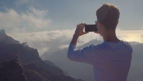 Ένας νεαρός άνδρας με ένα smartphone στα χέρια του αναρριχήθηκε στην κορυφή του βουνού στην άκρη του νησιού και παίρνει το α απόθεμα βίντεο