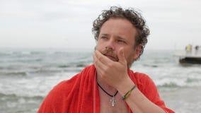 Ένας νεαρός άνδρας με μια γενειάδα και μπλε μάτια στο υπόβαθρο της θάλασσας μετά από τις αφές και τα κτυπήματα λουσίματος η γενει απόθεμα βίντεο
