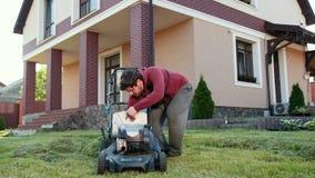 Ένας νεαρός άνδρας με μια γενειάδα, που καθαρίζει έναν θεριστή χορτοταπήτων, κοντά σε ένα μεγάλο όμορφο σπίτι φιλμ μικρού μήκους
