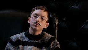 Ένας νεαρός άνδρας με τα γυαλιά και ένα λεπτό mustache κάθεται σε μια μαύρη καρέκλα δέρματος, που χάνεται στη σκέψη Ένας έξυπνος  απόθεμα βίντεο