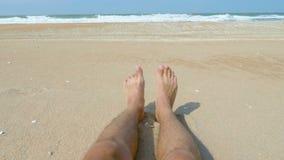 Ένας νεαρός άνδρας με τα τριχωτά πόδια βρίσκεται σε μια αμμώδη παραλία απόθεμα βίντεο