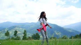 Ένας νεαρός άνδρας με τα dreadlocks που παίζουν με ένα πρότυπο αεροπλάνο στα βουνά απόθεμα βίντεο