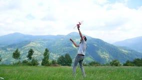 Ένας νεαρός άνδρας με τα dreadlocks που παίζουν με ένα πρότυπο αεροπλάνο στα βουνά φιλμ μικρού μήκους