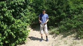 Ένας νεαρός άνδρας με την εγκεφαλική παράλυση ταξιδεύει Πίσω από το σακίδιο πλάτης, που περνά από τα ξύλα με ένα σακίδιο πλάτης κ απόθεμα βίντεο