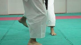 Ένας νεαρός άνδρας με τις πολεμικές τέχνες goju-Ryu μυϊκών σωμάτων και μιας άσκησης γυναικών karate- απόθεμα βίντεο