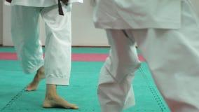 Ένας νεαρός άνδρας με τις πολεμικές τέχνες goju-Ryu μυϊκών σωμάτων και μιας άσκησης γυναικών karate- φιλμ μικρού μήκους