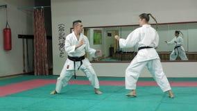 Ένας νεαρός άνδρας με τις πολεμικές τέχνες goju-Ryu μυϊκών σωμάτων και μιας άσκησης γυναικών karate-κάνει έξοχο σε αργή κίνηση φιλμ μικρού μήκους