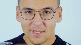 Ένας νεαρός άνδρας ντύνει τα γυαλιά και εξετάζει τη κάμερα απόθεμα βίντεο