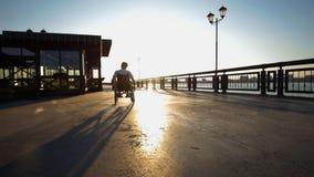 Ένας νεαρός άνδρας οδηγά μια αναπηρική καρέκλα στην προκυμαία στο υπόβαθρο ενός όμορφου θερινού ηλιοβασιλέματος στοκ φωτογραφίες με δικαίωμα ελεύθερης χρήσης