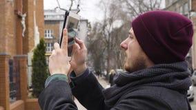 Ένας νεαρός άνδρας παίρνει μια φωτογραφία της εκκλησίας με μια ταμπλέτα απόθεμα βίντεο