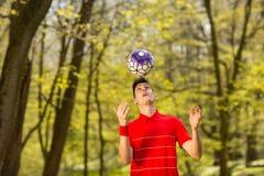 Ένας νεαρός άνδρας παιχνίδια στα κόκκινα μπλουζών με μια σφαίρα ποδοσφαίρου στο πράσινο πάρκο r στοκ φωτογραφία