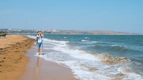 Ένας νεαρός άνδρας περπατά κατά μήκος της αμμώδους παραλίας και πυροβολεί seagull σε ένα κινητό τηλέφωνο απόθεμα βίντεο