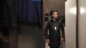 Ένας νεαρός άνδρας που κουμπώνει το σακάκι του και που εξετάζει στον καθρέφτη ένα κατάστημα ιματισμού απόθεμα βίντεο