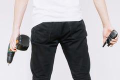 Ένας νεαρός άνδρας που κρατά walkie-talkie και ένα τρυπάνι, ένα κατσαβίδι r στοκ φωτογραφία