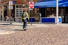 Ένας νεαρός άνδρας που οδηγά skateboard OneWheel στην περιοχή αγοράς Fulton, Σικάγο Φιλική μεταφορά Eco στοκ εικόνες