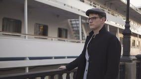 Ένας νεαρός άνδρας που στέκεται κοντά στο σκάφος που φαίνεται dval με ένα σοβαρό πρόσωπο απόθεμα βίντεο
