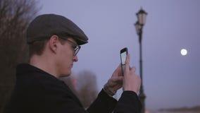 Ένας νεαρός άνδρας που στέκεται σε μια γραφική θέση από τον ποταμό στο ηλιοβασίλεμα παίρνει ένα τοπίο με τη βοήθεια ενός smartpho απόθεμα βίντεο