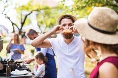 Ένας νεαρός άνδρας που τρώει ένα χάμπουργκερ σε έναν οικογενειακό εορτασμό ή ένα κόμμα σχαρών έξω στοκ φωτογραφία