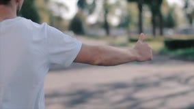 Ένας νεαρός άνδρας που χαιρετά ένα ταξί από την πίσω άποψη απόθεμα βίντεο