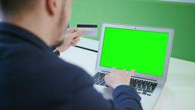 Ένας νεαρός άνδρας που χρησιμοποιεί ένα lap-top με μια πράσινη οθόνη Στοκ Εικόνες
