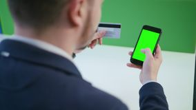 Ένας νεαρός άνδρας που χρησιμοποιεί ένα Smartphone με μια πράσινη οθόνη Στοκ φωτογραφίες με δικαίωμα ελεύθερης χρήσης
