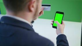 Ένας νεαρός άνδρας που χρησιμοποιεί ένα Smartphone με μια πράσινη οθόνη Στοκ Φωτογραφία