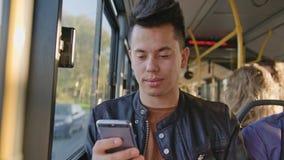 Ένας νεαρός άνδρας που χρησιμοποιεί ένα Smartphone στο λεωφορείο Στοκ Φωτογραφία