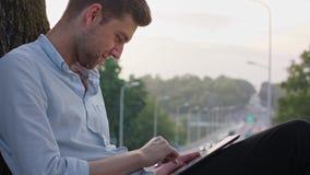 Ένας νεαρός άνδρας που χρησιμοποιεί μια ταμπλέτα υπαίθρια απόθεμα βίντεο