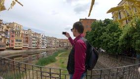 Ένας νεαρός άνδρας πυροβολεί ένα βίντεο με ένα smartphone κοντά στον ποταμό Onyar Girona, Ισπανία απόθεμα βίντεο