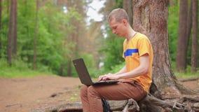 Ένας νεαρός άνδρας σε ένα δάσος εργάζεται σε ένα lap-top απόθεμα βίντεο